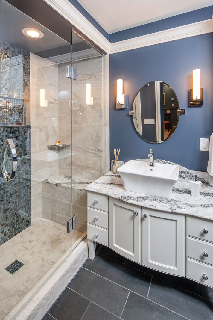 A regal looking bathroom with a white crystal cabinet, vessel sink, Cambria countertops, and a metallic-gray tile backsplash to the large, frameless shower.