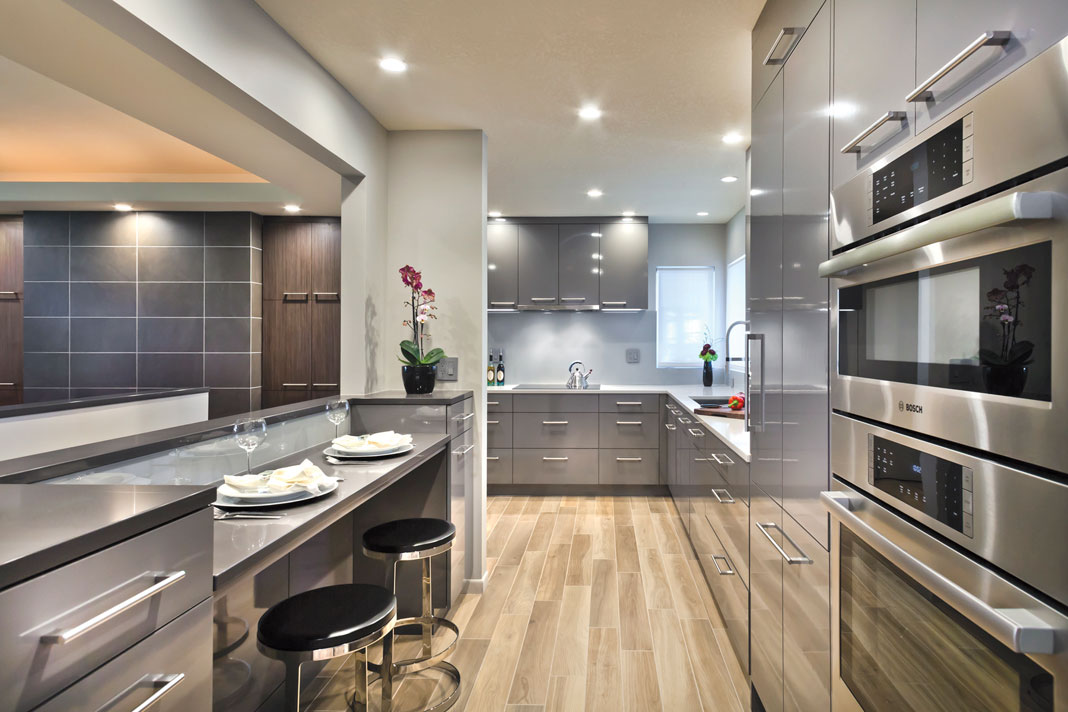 A gray and glossy taupe color palette kitchen with porcelain tile floors, breakfast bar, and custom cabinetry.