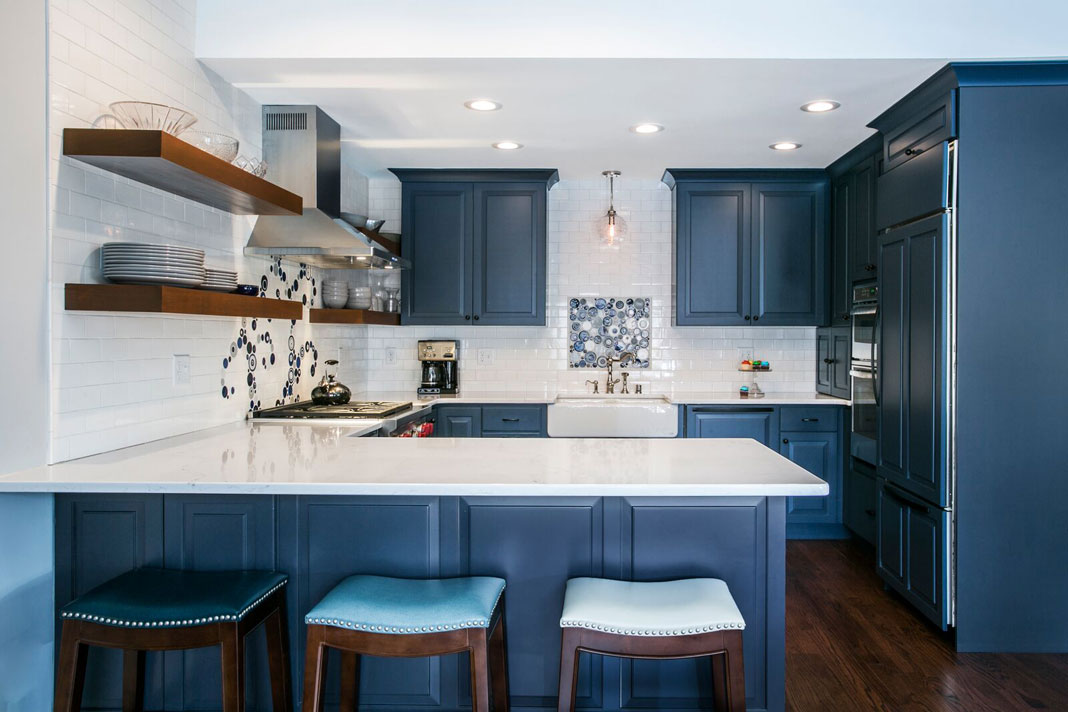 A blue kitchen with white walls, floating shelves, and dark wood flooring.