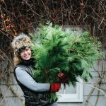 A portrait of Christine Hoffman, founder of Twin Cities Flower Exchange, holding green plants.