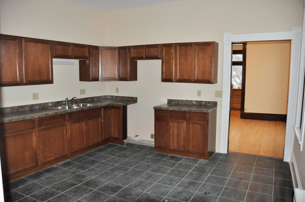 A before photo of a kitchen showing outdated tile, cabinetry, and countertops.