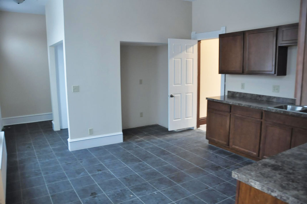 An outdated kitchen showing a cramped mudroom, and outdated tile, cabinetry, and countertops.