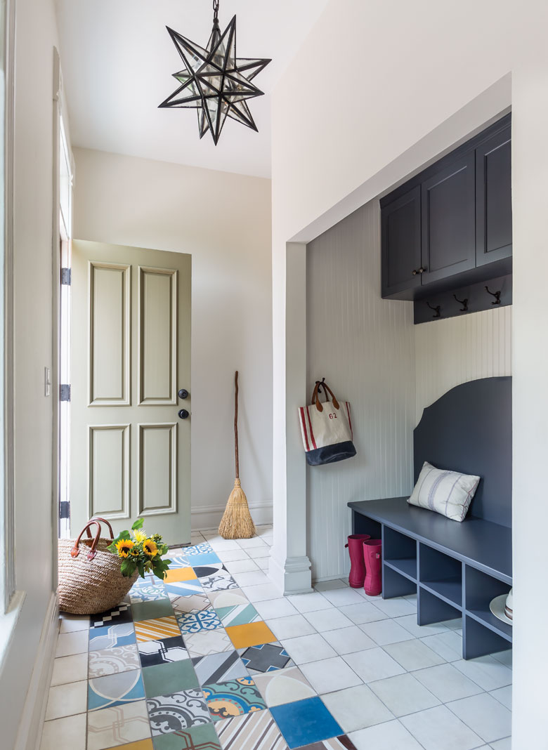 """The back entry of home with a tile """"rug,"""" bench, and places for shoes."""
