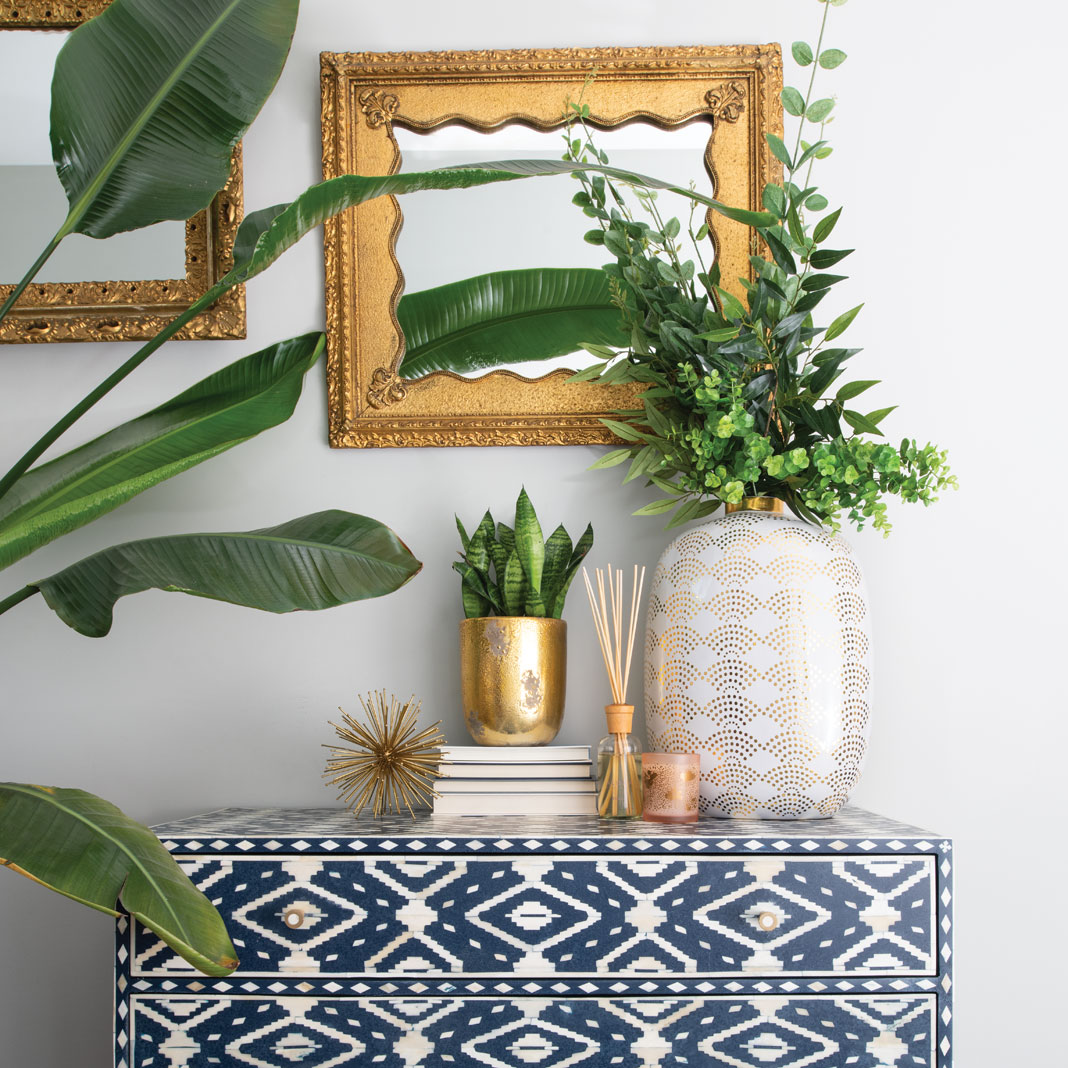 A graphic dresser, vintage gold mirrors, a vase from Martin Patrick 3, and plenty of green plants make a bright bohemian vignette in the home of Jen Biswas, owner of Paisley + Sparrow.