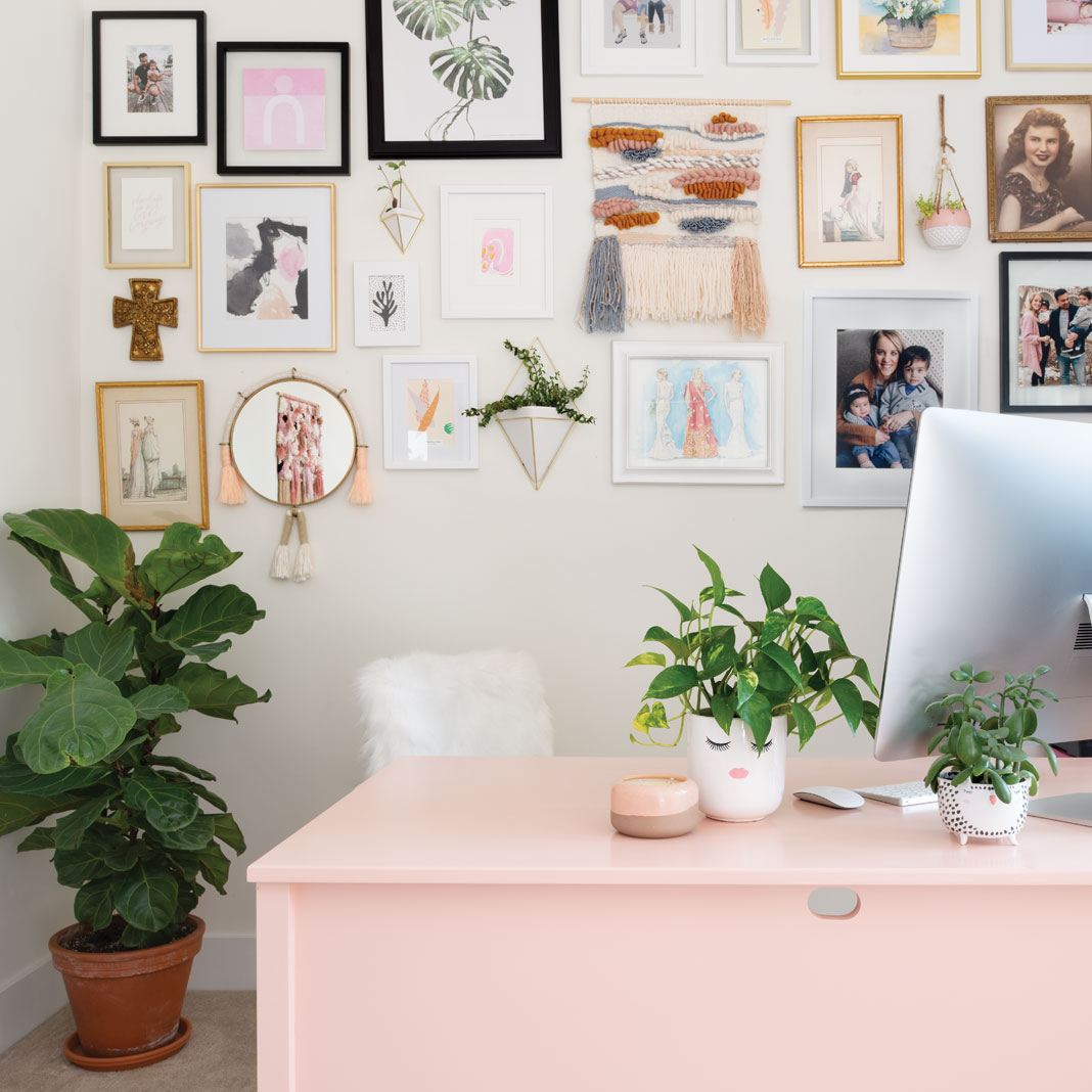 A wall full of framed photos and a pink desk with computer on top inside the office Jen Biswas, owner of Paisley + Sparrow.