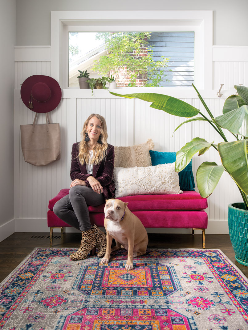 Jen Biswas of Paisley + Sparrow, with her rescue dog Chloe, sitting pretty on a custom upholstered bench from Anthropologie.