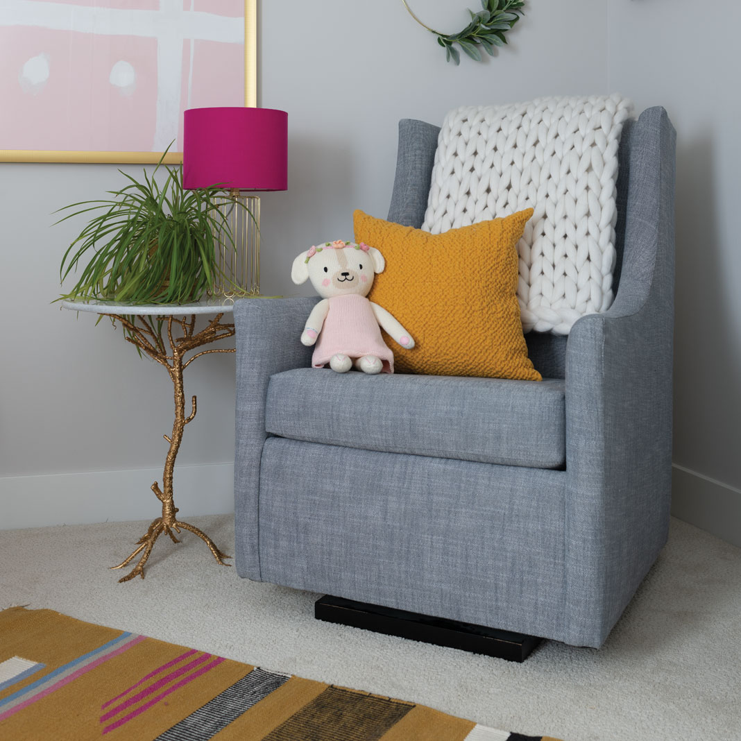 A rocking chair with a stuffed teddy bear in the home Jen Biswas, owner of Paisley + Sparrow.