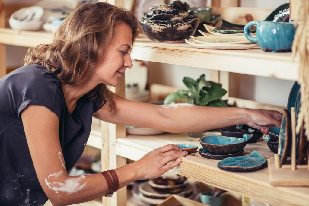 Woman stocking shelves with pottery