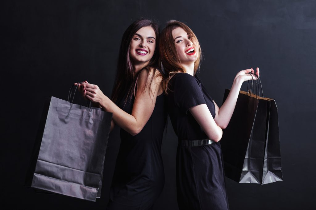 Elegant brunette womans wears black dress holding black shopping bags, black friday concept