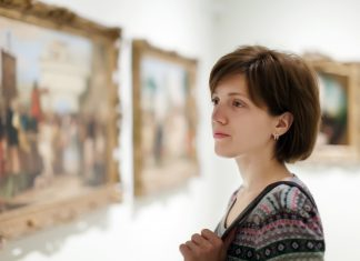 Woman looking at paintings/photos in a museum