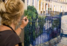 Lady artist at work painting a large acrylic artwork