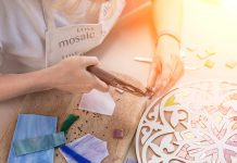 Hands working on new modern colorful mosaic at workshop.