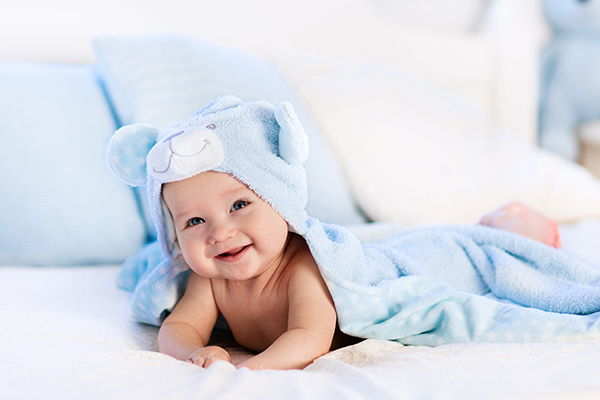 Promo image for the Minnesota Baby & Beyond Expo, showing a baby in a towel over their head laying on a blanket