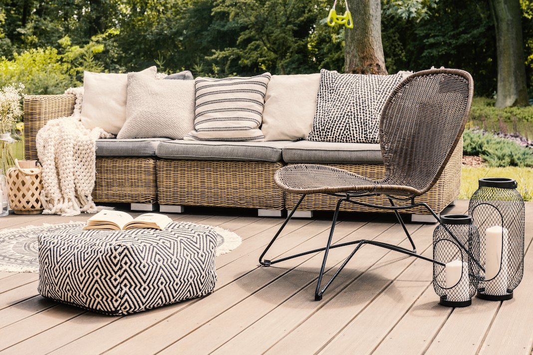 The patterned pouf and rattan chair are accented by the wire lanterns.