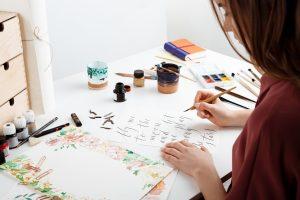 Girl writing calligraphy on postcards.