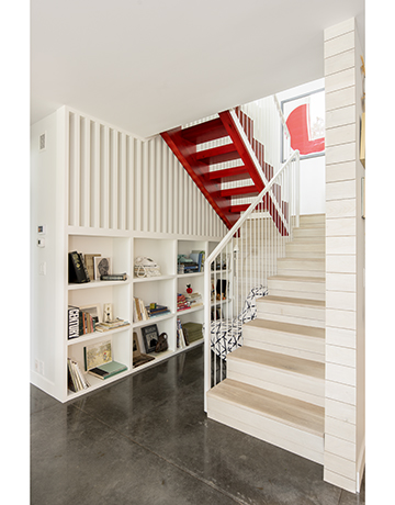 A white and red stairwell with nearby shelves