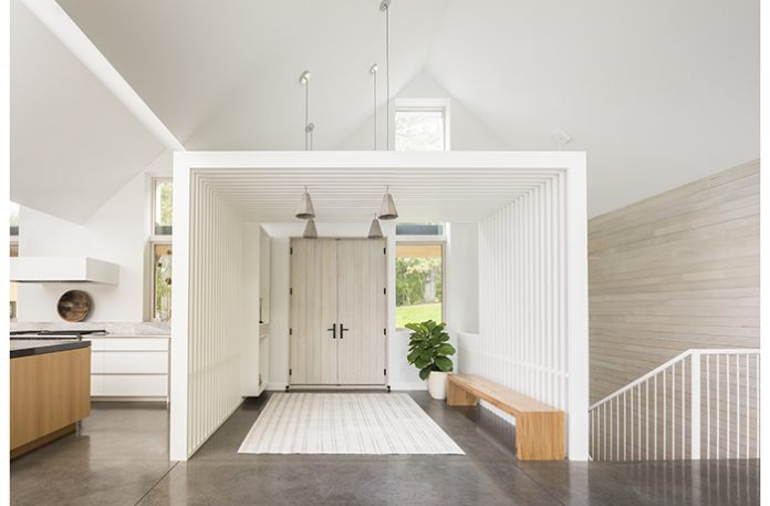 An entrance of a home that is mostly white with accents of wood