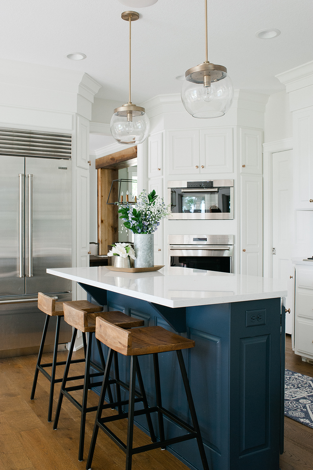 A white kitchen with navy island, stainless steel appliances, and accents of wood.