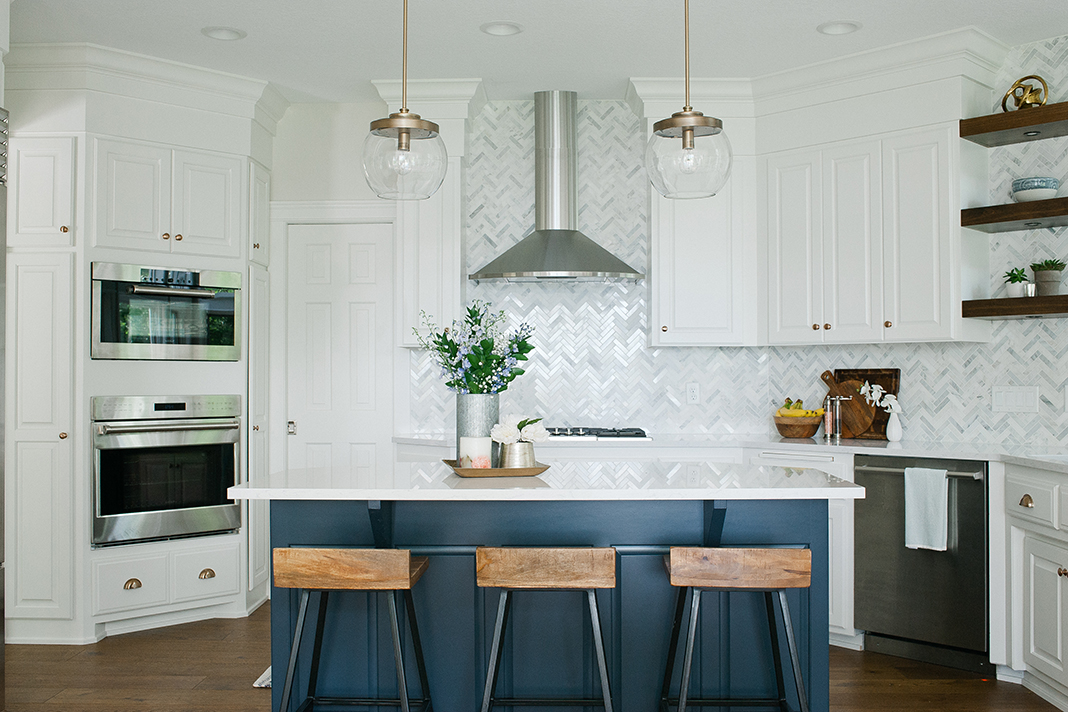 A white kitchen with navy island and Warners' Stellian appliances.
