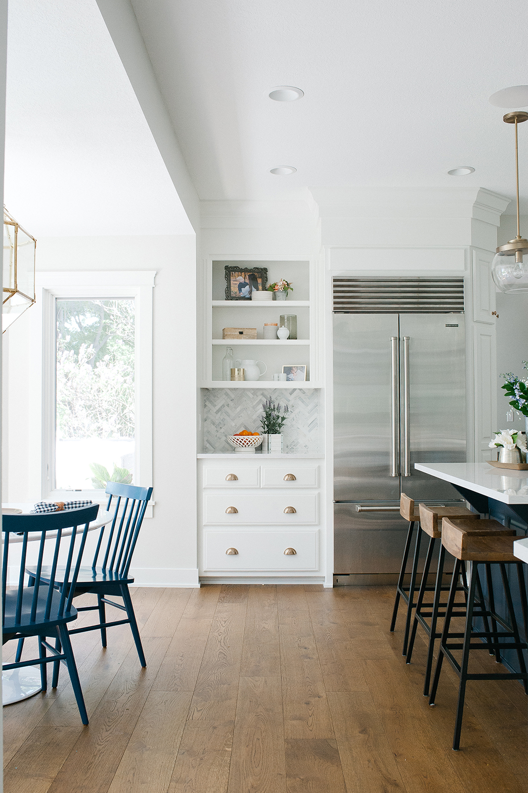 A white kitchen with a navy island, navy dining chairs, and a stainless steel refrigerator.