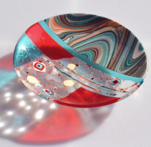 A turquoise, red, and clear glass bowl
