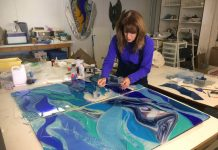 A woman creates artwork using colored glass