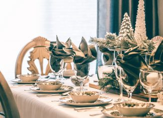A dining table with a green and white holiday tablescape.