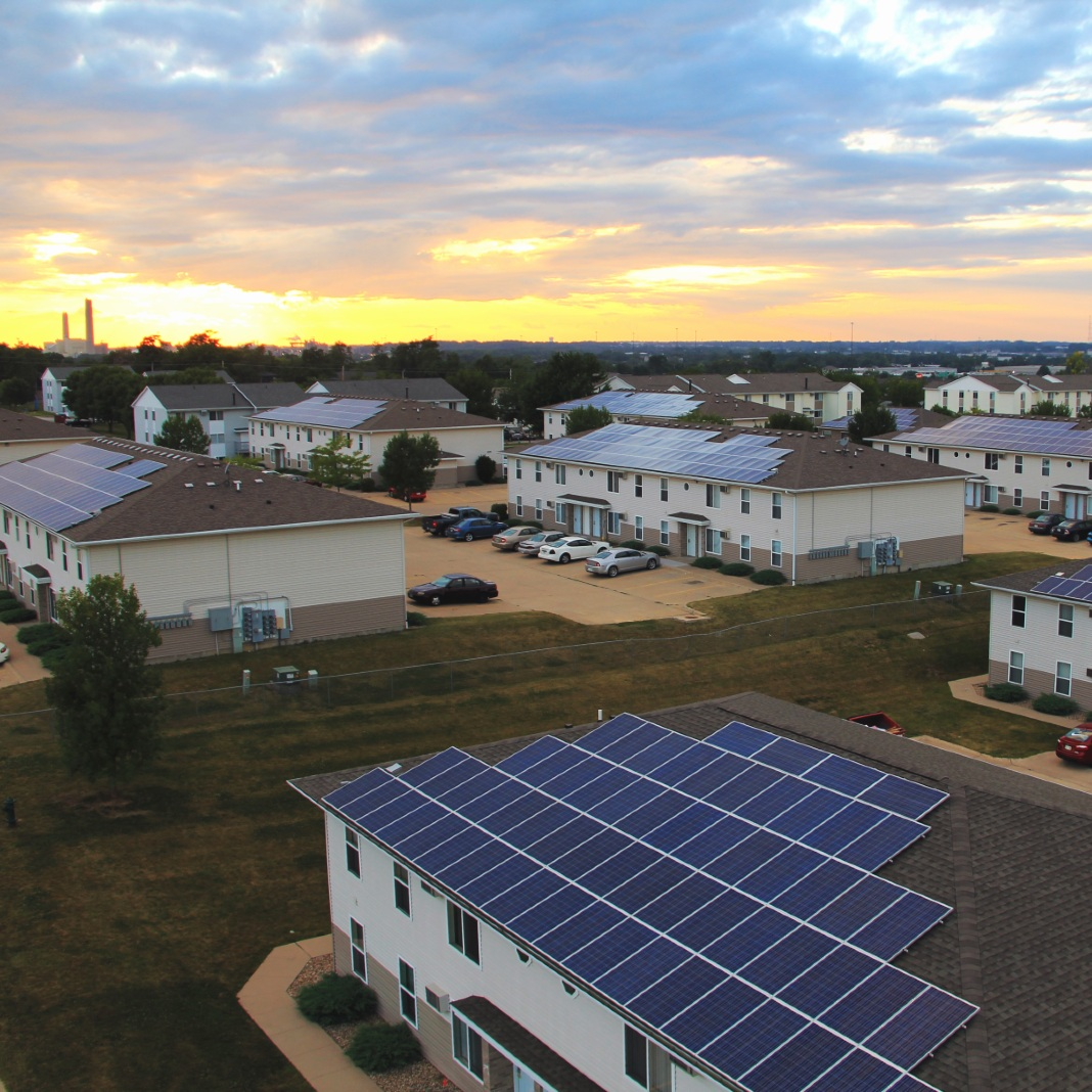 Several apartment buildings with solar panels on the roof