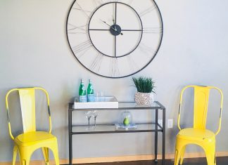Two yellow, metal chairs with a glass table between them and decorations on the table and wall