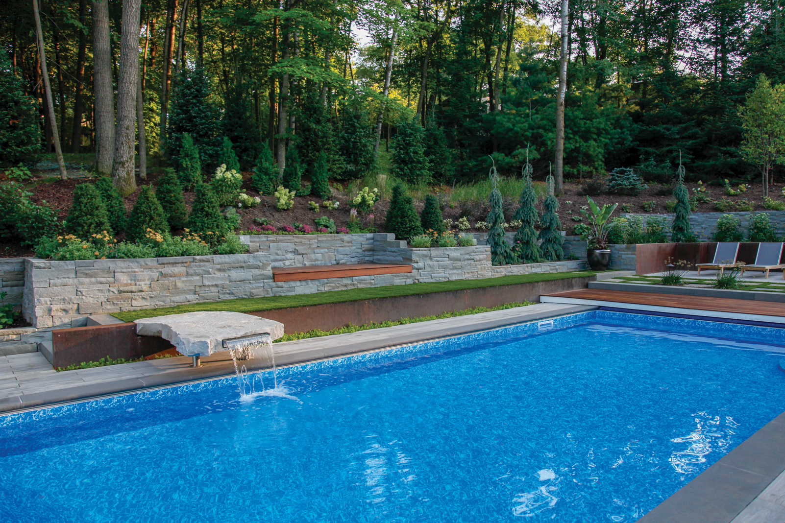 A bluestone slab complete with a miniature waterfall feature doubles as a jump-off point for the kids, adding a fun element to the pool area without sacrificing aesthetic.