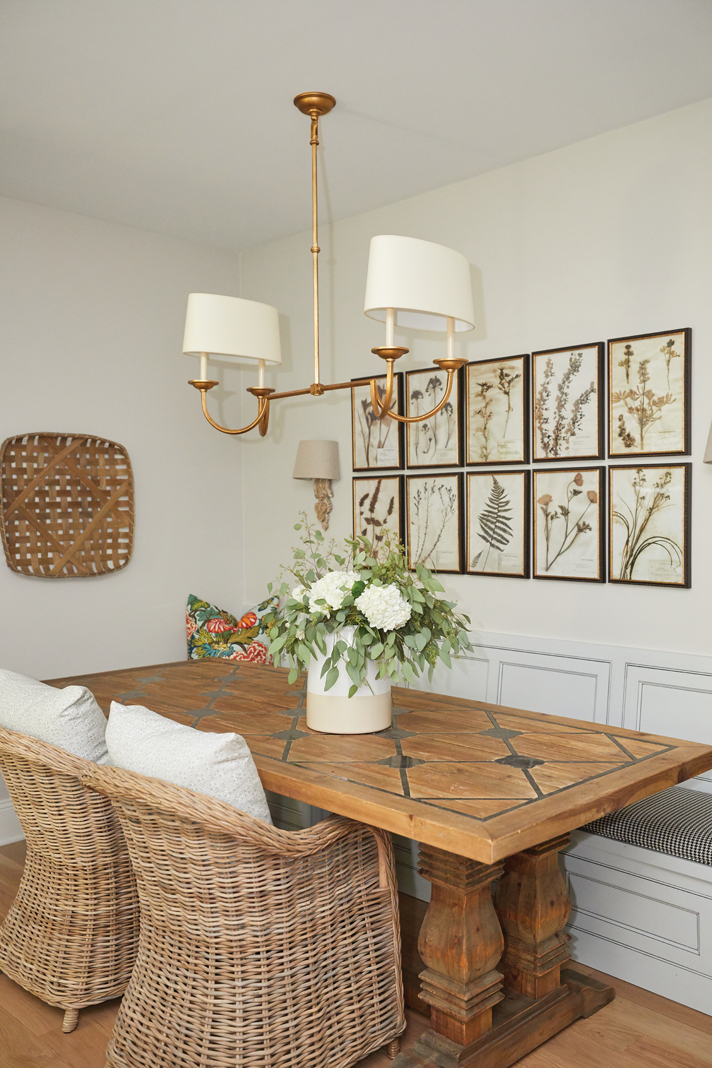 A framed set of botanical prints add a lovely design element to the nearby breakfast nook.