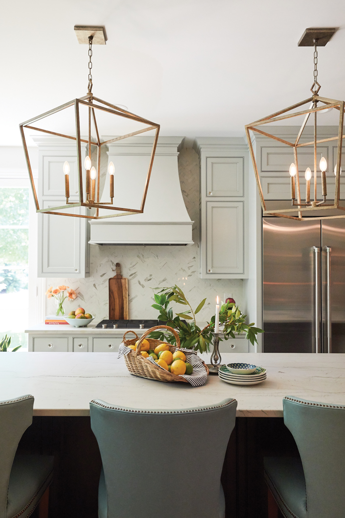 With brushed bronze lantern lights and cabinets painted a light cream, Keller's kitchen is a breath of fresh air and a perfect gathering space.