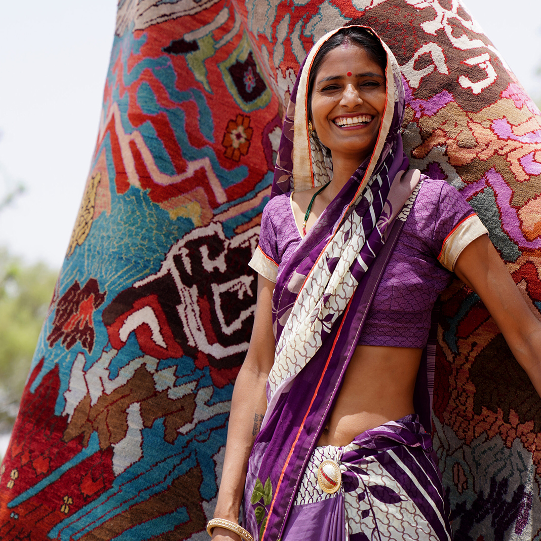Indian woman smiling and wearing purple, standing in front of a multicolored hand-knotted rug that is available at Cyrus Artisan Rugs