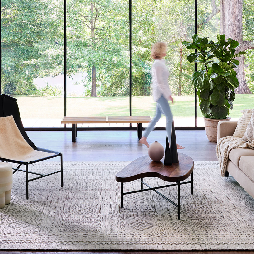 Woman walking through bright living room with light colored couch and chair and a tan wool rug from Cyrus Artisan Rugs