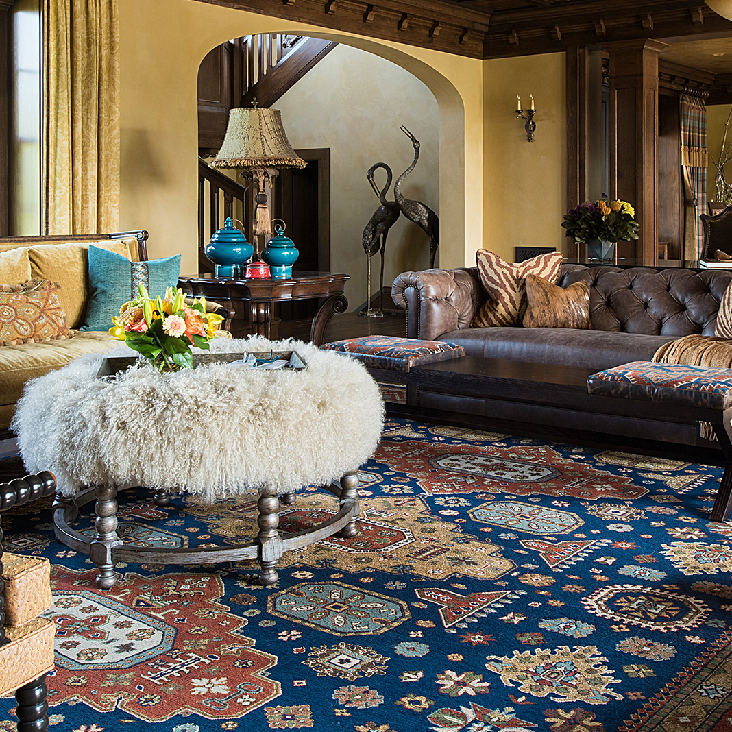 Living room with leather couches, fur covered coffee table, and an ornately designed orange and blue rug from Cyrus Artisan Rugs