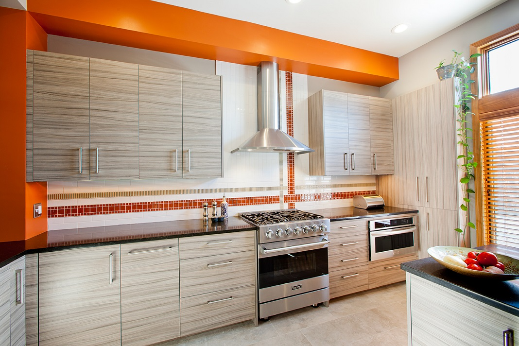 Bright, modern kitchen with light wooden cabinets, black countertops, and orange accents. Designed and built by Sawhill.