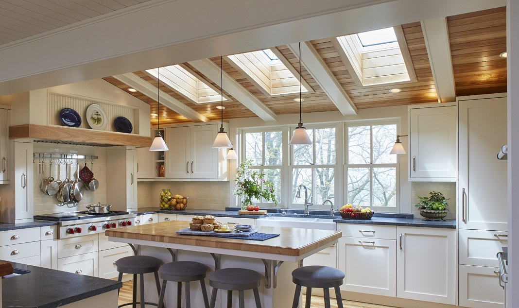 Open kitchen with skylights, butcher block countertop on the large island, gray countertops on the surrounding work tops, and white cabinets. Designed and built by Sawhill.