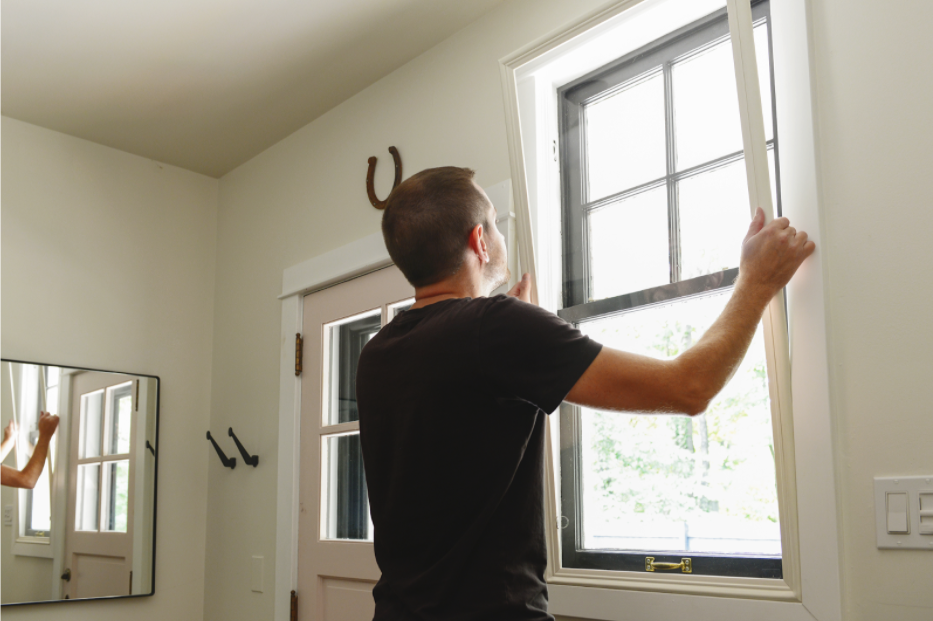 A man soundproofing a window
